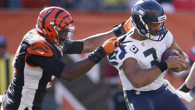 Cincinnati Bengals defensive end Carlos Dunlap (96), left, sacks Seattle Seahawks quarterback Russell Wilson (3) in in the third quarter during the NFL game between the Seattle Seahawks and the Cincinnati Bengals, Sunday, Oct. 11, 2015, at Paul Brown Stadium in Cincinnati, Ohio. The Bengals defeated the Seahawks 27-24 in overtime.