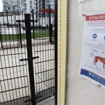 In this Thursday, April 16, 2015 photo, a sign warning of canine respiratory illness is posted at a dog park in Chicago. Experts say doggie day care contributed to an epidemic of dog flu in Chicago that is spreading in the Midwest. The illness is caused by an Asian viral strain, which could arise in other U.S. urban areas. In Chicago, it gained a foothold in doggie day care centers and got an extra boost from spring break when pets were boarded in kennels. (AP Photo/M. Spencer Green)