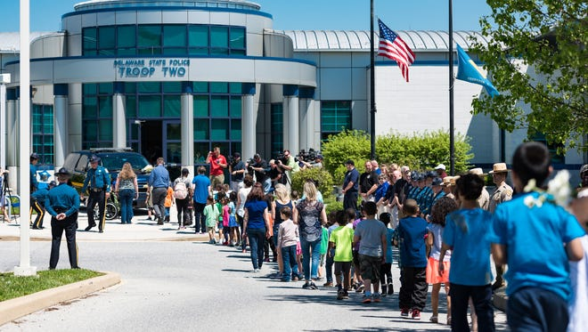 About 700 kindergarten through fifth-grade students and faculty from Keene Elementary School form a procession to Delaware State Police Troop 2 in Glasgow to place flowers and cards of love and appreciation at a memorial for Cpl. Stephen Ballard.