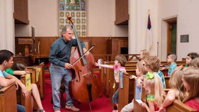 Youth at art and music camp at Floral Heights United Methodist Church in this file photograph from 2015 learned all about playing the bass from David Holcomb. Churches are getting ready for this summer's slate of vacation Bible school.