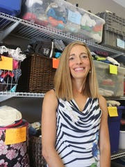 Founder Jessica Goodall stands in front of racks of