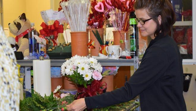 Amy Garner works on a Valentine's Day floral arrangement Friday at University Florist.