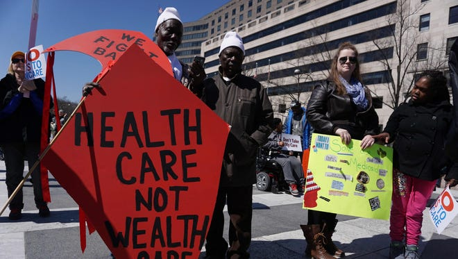 Health care activists hold placards during a rally at Freedom Plaza on March 23, 2017, in Washington.