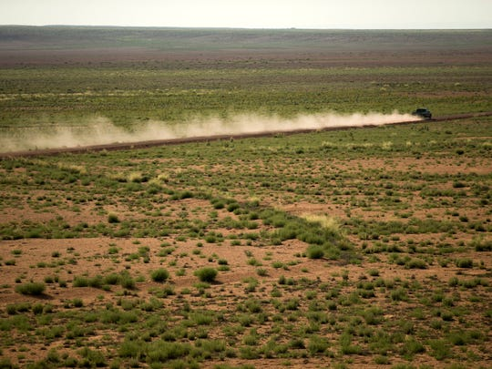 A pickup truck kicks up dust while driving on a dirt road outside of Leupp, Ariz., on the Navajo Nation.