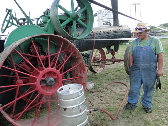 Andy Schmitz, Slinger, steams some corn using the steam from his 1916 Case 50 hp steam engine during a past Dodge County Antique Power Club show. This year's show is being cancelled due to COVID-19.