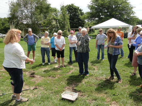 Women gather around to learn more about healthy soil during a demonstration by Carol Schutte of the Women, Food and Ag Network.