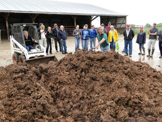 In this file photo, a farmer turns a compost pile while observers learn more about how to create an ideal material to spread on pastures as a soil enhancer. Leaves can be part of the compost heap.