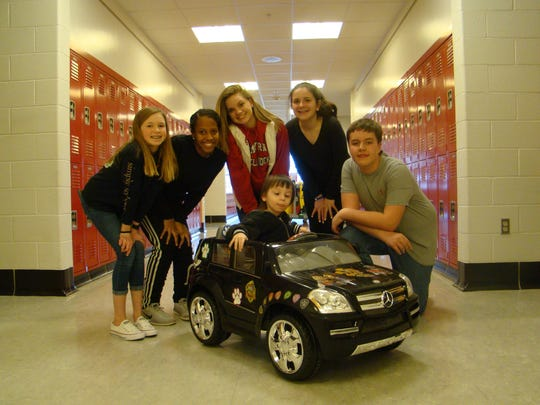 Marcos, a third-grader in the Smyrna School District's early childhood education program, poses with the team of middle schoolers that built his new GoBabyGo car.