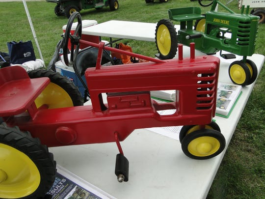 Rare 1949 coffin block engine (red) toy pedal tractor (front). The green model (back) replaced it featuring the 2 cylinder engine.