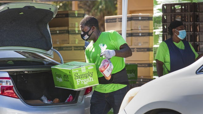 Volunteers with United Haitian Baptist Church's Food Ministry load cars with food from Feeding South Florida Wednesday during a drive-thru distribution at the church in West Palm Beach.  The organization serves 400-600 people every Wednesday, starting at 8a.m.