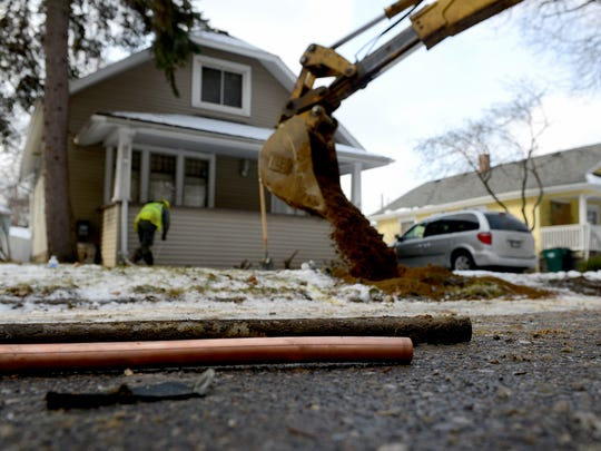 LSJ file photo of a piece of an old lead water pipe sitting next to a new copper pipe as Lansing Board of Water & Light crews replace the pipes at a home in Lansing in 2016.
