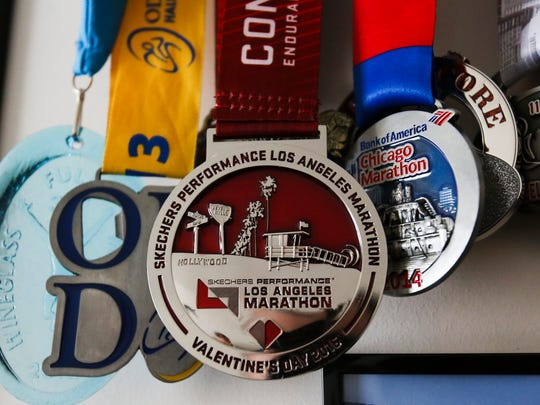 Kathy Nguyen's Los Angeles Marathon finisher's medal, displayed with other trophies from sporting successes, holds a special place among the mementoes in her family's Newark home because it represents her recovery from a dangerous brain condition and surgery less than a year prior to the race.