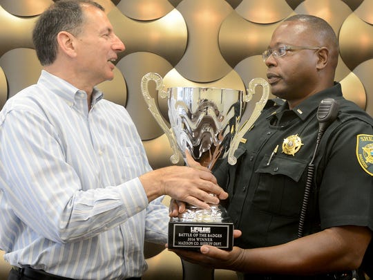 Lifeline Blood Services Director Joe Schifano presents Lt. Cleven Davis with the Battle of the Badges trophy Thursday. The Madison County Sheriff's Office won the competition.