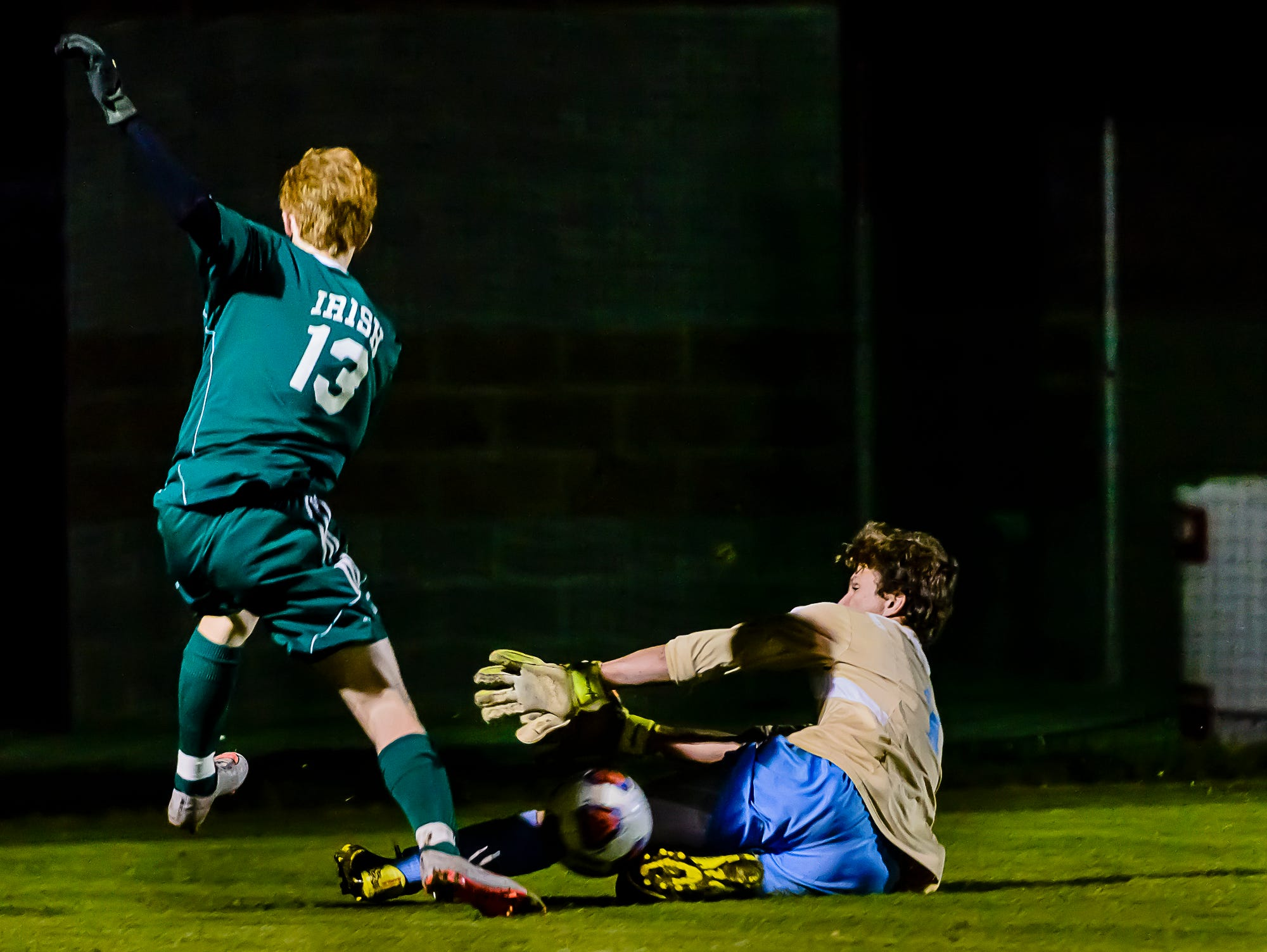 Mattjew Benivegna ,right, Lansing Catholic goalie slides to block a shot on goal by Brenden Cupchak ,13, of Gabriel Richard late in the 1st half of their Division 3 regional quarterfinal game Tuesday October 25, 2016 in Williamston. The ball would pop oer Benivegna and give Juan Sancho of Gabriel Richard a wide open net but the ball would miss wide right. KEVIN W. FOWLER PHOTO