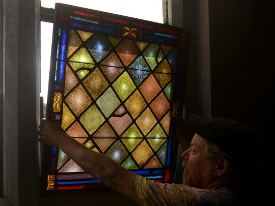 Lee Gaugh shows the size of the bottom panel of one of the stained glass windows inside of the old West Jackson Baptist Church on W. Deaderick St. Gaugh was given the task of removing and preserving the stained glass.