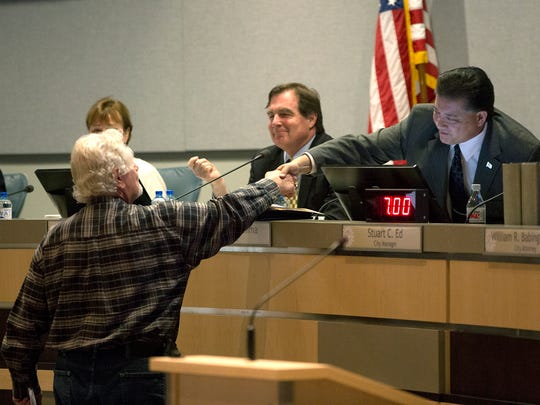 """Mayor Ken Miyagishima, shakes hands with former Athletics Director of Las Cruces Public Schools Harold """"Bump"""" Elliot after a resolution approving a memorial roadway designation for """"Coach Jim Bradley Championship Way, Along Tashiro Dr and N. Motel Blvd. Tuesday February 21, 2017 at the Las Cruces City Council meeting."""