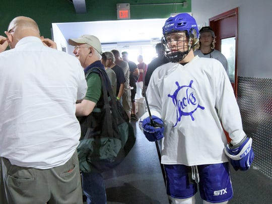 Skipjacks Hockey Club member Justin Fowlkes, 17, and teammates head to the locker room past the line of people waiting to get into the Book Nook Bonanza at the York City Ice Arena Friday, June 23, 2017.