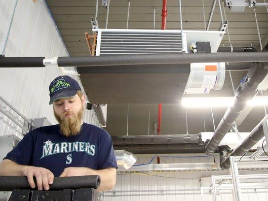 Chriastian Cetlinski, of Shelton, works on insulating