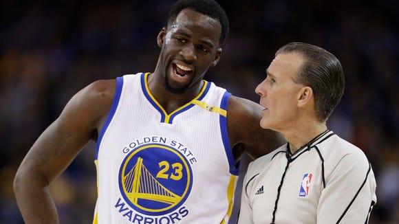 Golden State Warriors' Draymond Green (23) argues a