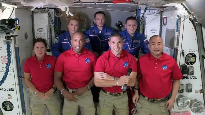 In this frame grab from NASA TV, SpaceX Dragon crew, from front left to right, Shannon Walker, Victor Glover, Mike Hopkins and Soichi Noguchi stand with International Space Station crew Kate Rubins, from back left, Expedition 64 commander Sergey Ryzhikov and Sergey Kud-Sverchkov during a welcome ceremony, early Tuesday, Nov. 17, 2020. The Dragon arrived and docked at the ISS late Monday.