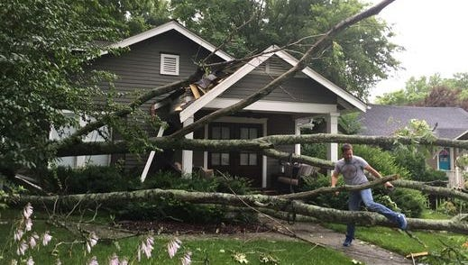 Homeowner Chuck Ingram walks out of his home in July after a tree fell Franklin, Tenn., south of Nashville. Nashville was ranked as the USA's windiest city in 2016.