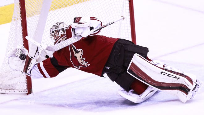Arizona Coyotes' goalie Louis Domingue dives to make a block as the Arizona Coyotes face off against the Vancouver Canucks on Wednesday, Feb. 10, 2016, at Gila River Arena in Glendale, Ariz.