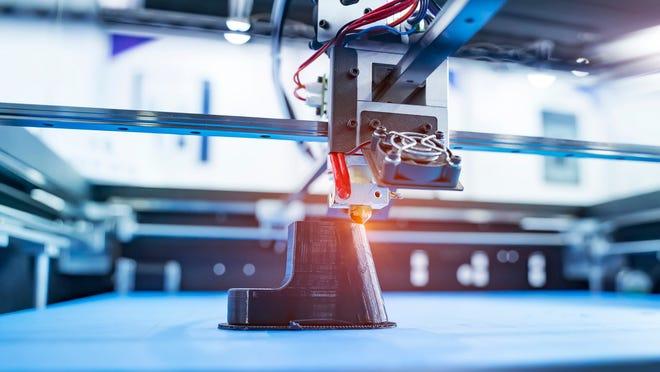 A close-up of a 3D printer producing a component.
