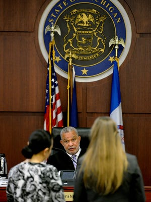 This LSJ file photo shows a defendant and court-appointed attorney standing before a judge in an Ingham County courtroom.