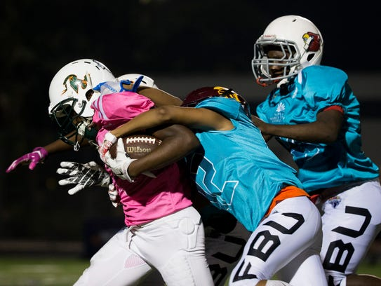 Team Tampa's Joquez Smith, left, carries the ball against