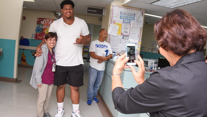 "Guam Memorial Hospital Registered Nurse Angie Guingao smiles as she tries to ""measure up"" to Chamorro NFL draft pick Zach Banner during his visit to the Guam Memorial Hospital on Friday, July 7, 2017."
