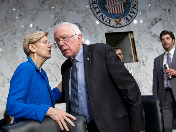 Sen. Elizabeth Warren, D-Mass., speaks with Sanders