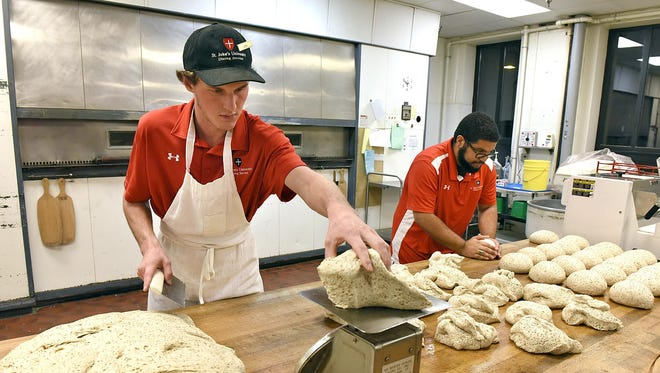 Jared McComber weights out dough and Rafael Roman forms them into balls as they prepare a 60-loaf batch of bread Wednesday at St. John's University.