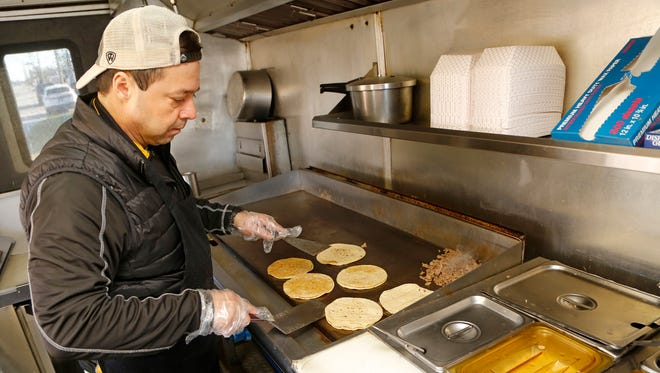 Owner Jose Alfonso Lopez prepares steak tacos inside the L Kora food truck Wednesday, December 6, 2017, on McCarty Lane next to Wabash National.
