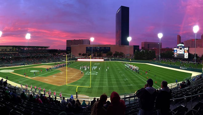 Fans have a unique view of the game with the skyline of Indianapolis as a backdrop during the first half of action of an inaugural IHSAA varsity football game being played at Victory Field in Indianapolis, Friday, October 2, 2015.