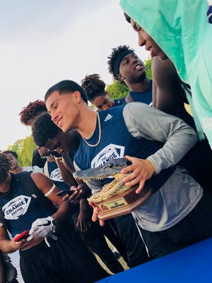 Immokalee sophomore quarterback RJ Rosales holds the gator trophy after leading his team to nine wins and the championship at the Battle of the Swamp 7-on-7 competition in Gainesville on Saturday.