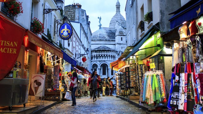 Tourists and locals browse shops in Paris.