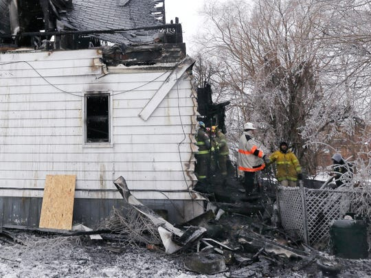Firefighters comb through the rear of a burned house, Tuesday, Feb. 17, 2015 in Hamtramck, Mich. Children are among four people who died early Tuesday in a house fire near Detroit that was so intense that rescuers who rushed inside the home couldn't reach them in time, officials said.