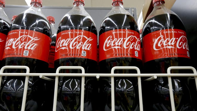 FILE- In this Aug. 8, 2018, file photo bottles of Coca-Cola sit on a shelf in a market in Pittsburgh.  The Coca-Cola Co. said on Thursday, Oct. 22, 2020, it saw gradual improvement in the third quarter, as it turned its focus to emerging leaner from the global pandemic. Atlanta-based Coke said its revenue fell 9% to $8.7 billion.