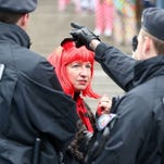 Members of the German police talk to a woman wearing a costume in front of the central railway station in Cologne, on Feb.4.