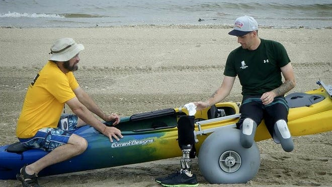 Kevin Carr, left, helps an amputee use adaptive paddling gear Carr invented to help people with disabilities be able to canoe and kayak. Carr has two companies: Chosen Valley Canoe Accessories, and Creating Ability, based where he lives in Chatfield, Minnesota.