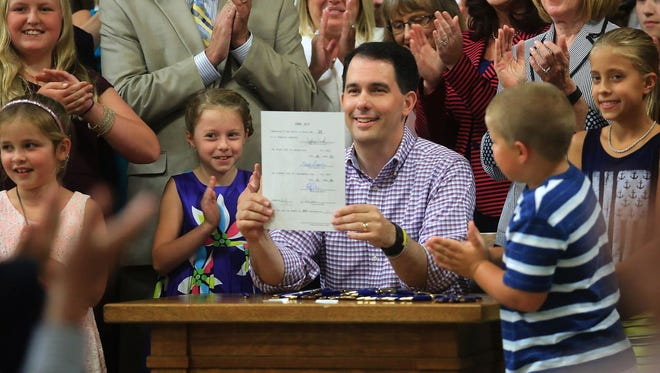 Wisconsin Governor Scott Walker displays a signed 2015-2017 state budget Sunday during a ceremony on the production floor of Valveworks USA in Waukesha.