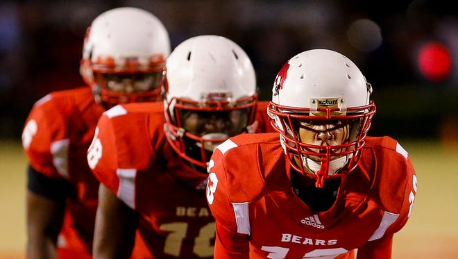 With his teammates in I formation behind him, Butler QB Chaz Burks (13) inspects the PRP defense.