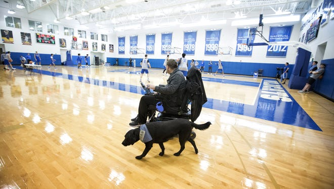Kevin Massey with his dog, Aria, on a UK basketball court Nov. 30.   Massey's eligibility as a student-manager has expired, so now he goes to UK basketball practice just to watch and get fist-pounds from his super-tall friends.
