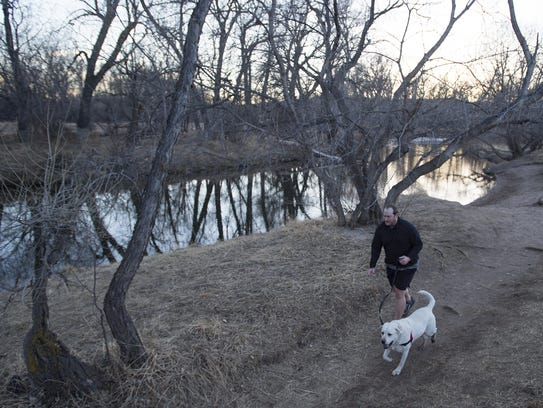 A man runs alongside the Poudre River in Fort Collins