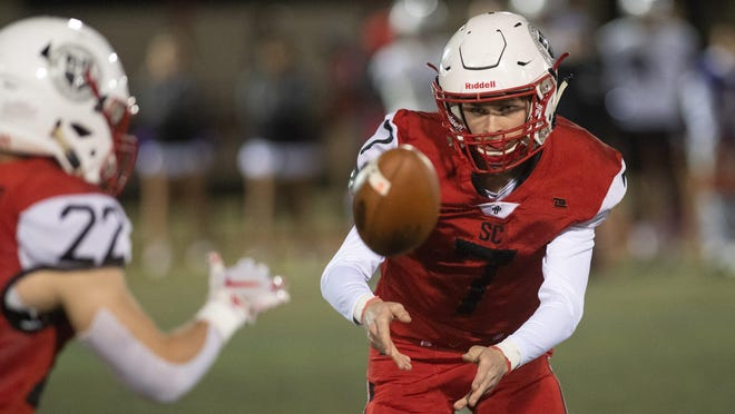 St. Charles' Andy Mason, right, pitches the football to Luke Eversole during the Cardinals' game against DeSales last October. St. Charles on Monday suspended its football and soccer seasons.