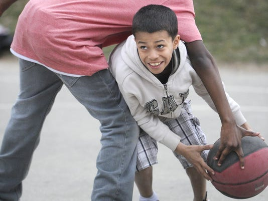 10-year-old Jose Flete fights through defensive pressure while playing basketball in March at Lincoln Park in York. If you've become too serious about fitness, try playing like a kid. (Daily Record/Sunday News -- Jason Plotkin)