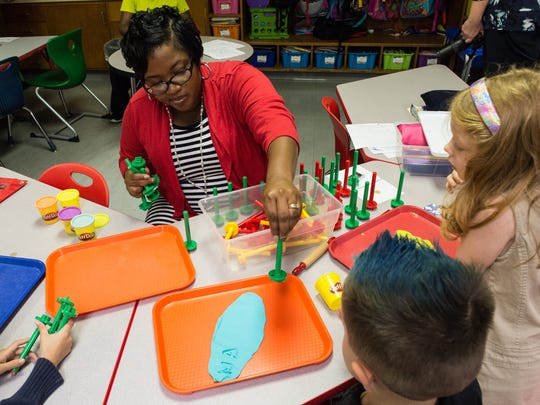 Chipman Elementary instructional assistant Ebonie Scarborough works with students on a name building exercise using Play-Doh and stamps on Thursday, Sept. 14, 2017.