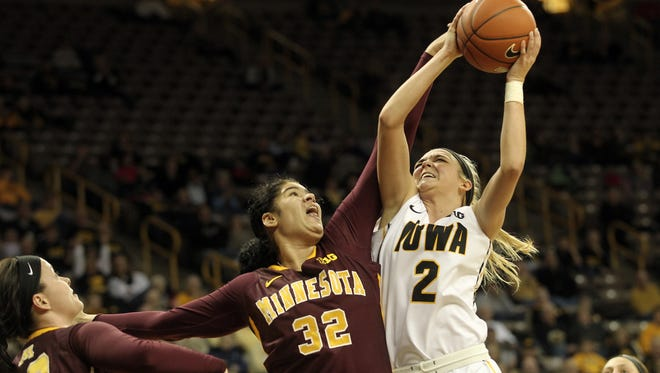 Iowa's Ally Disterhoft draws a foul from Minnesota's Amanda Zahui B. during their game at Carver-Hawkeye Arena on Wednesday, Jan. 8, 2014.