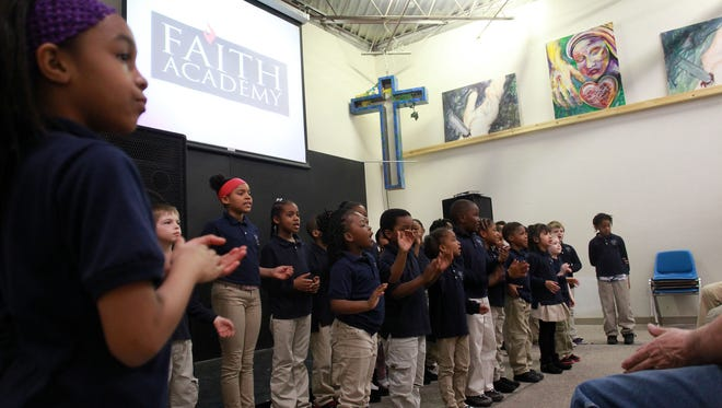 Students at Faith Academy sing to guests at their school on March 31, 2015.