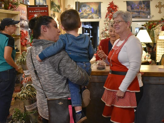 Alice Weinman and Brenda Barber, family owners of Victoria, are delighted by the reaction of a young customer to a sample of their candy.